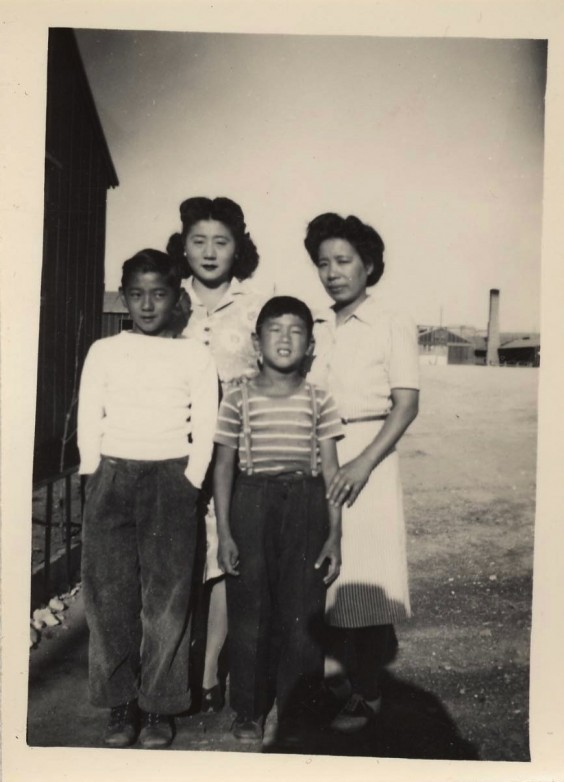 "From left: Fred Yoshitomo Sasaki, age twelve; Asako ""Mona"" Sasaki; John Tomoyoshi Sasaki, age eight; and unidentified friend and hatted shadow."